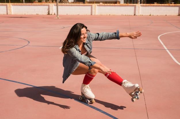 Giovane donna sorridente che indossa equilibratura femminile del pattinatore Foto Gratuite