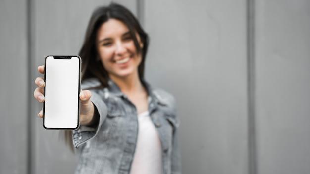 Giovane donna sorridente che mostra smartphone Foto Gratuite