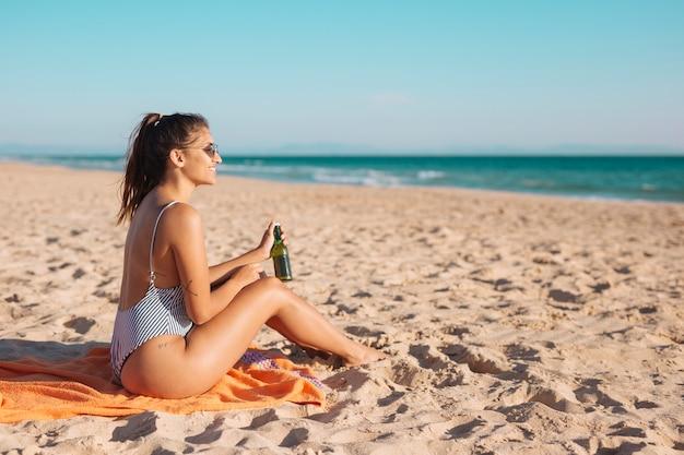 Giovane donna sorridente che si distende sulla spiaggia con birra Foto Gratuite
