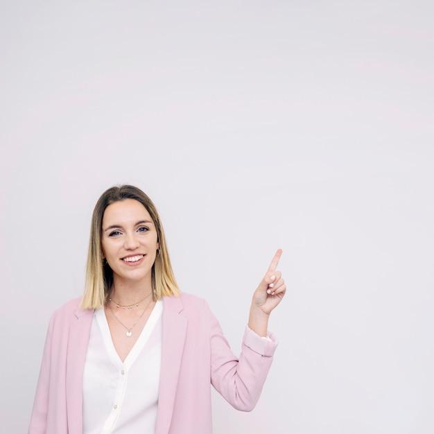 Giovane donna sorridente che si leva in piedi contro la priorità bassa bianca che indica verso l'alto Foto Gratuite