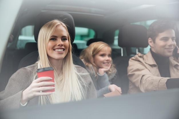 Giovane donna sorridente che si siede in automobile con la famiglia Foto Gratuite