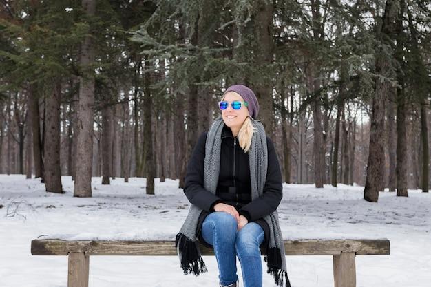 Giovane donna sorridente che si siede sul banco di legno nell'orario invernale alla foresta nevosa Foto Gratuite