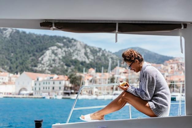 Giovane donna sorridente che si siede sulla piattaforma dell'yacht Foto Gratuite