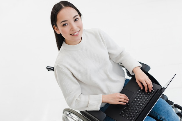 Giovane donna sorridente che si siede sulla sedia a rotelle facendo uso del computer portatile contro fondo bianco Foto Gratuite