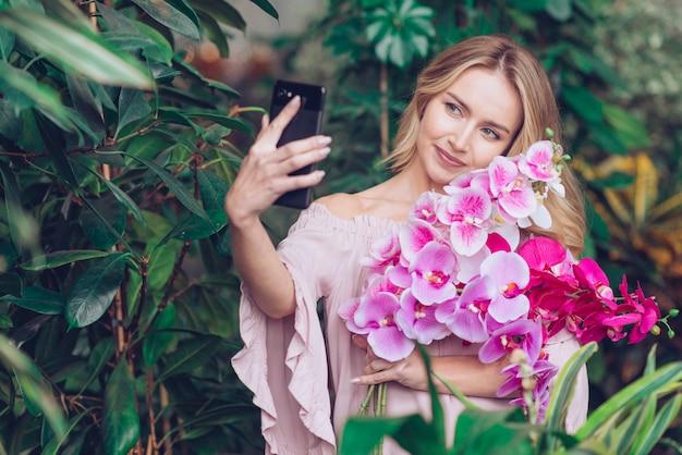 Giovane donna sorridente che tiene i bei rami dell'orchidea a disposizione prendendo selfie sullo smart phone Foto Gratuite