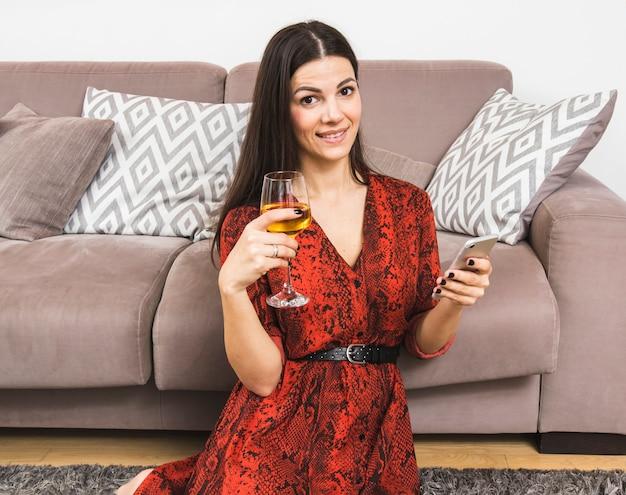 Giovane donna sorridente che tiene telefono cellulare e bicchiere di vino in mano seduto vicino al divano Foto Gratuite