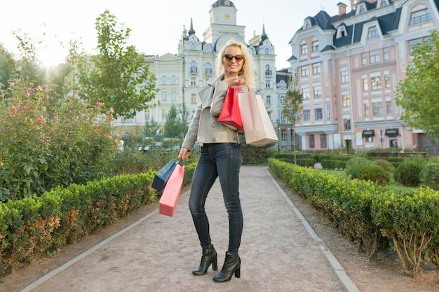 Giovane donna sorridente con borse per lo shopping Foto Premium