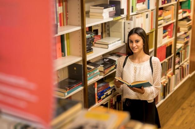 Giovane donna sorridente con il libro vicino allo scaffale per libri Foto Gratuite