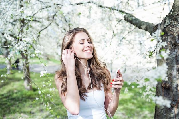 Giovane donna sorridente e con gli occhi chiusi, ascoltando la musica sul telefono Foto Premium