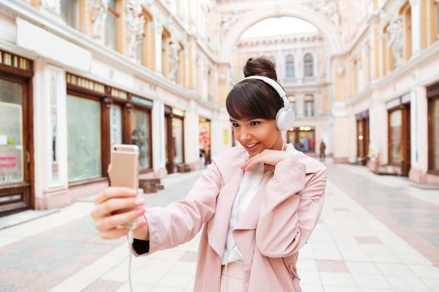 Giovane donna sorridente felice in cuffie che fanno la foto del selfie Foto Gratuite