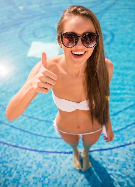 Giovane donna sorridente in bikini in piscina. Foto Premium