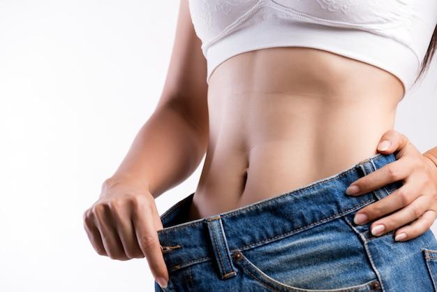 Giovane donna sottile in blue jeans oversize. donna adatta che indossa pantaloni troppo larghi Foto Premium
