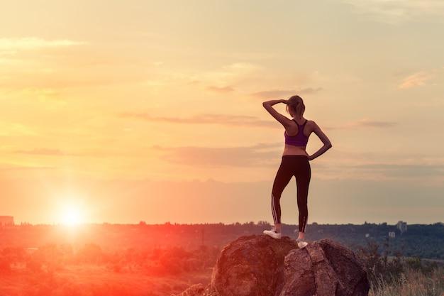 Giovane donna sportiva con le braccia alzate al tramonto Foto Premium