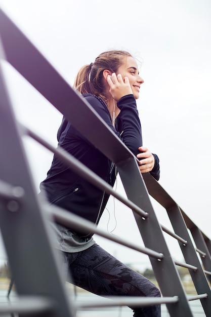 Giovane donna sportiva con le cuffie che si appoggia recinto e che distoglie lo sguardo all'aperto Foto Premium