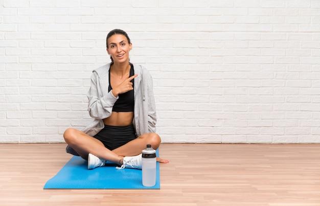 Giovane donna sportiva seduta sul pavimento con stuoia che punta il dito verso il lato Foto Premium