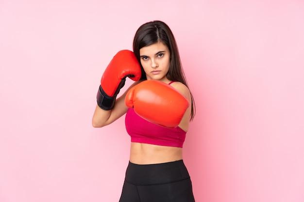 Giovane donna sportiva sopra la parete rosa con guantoni da boxe Foto Premium