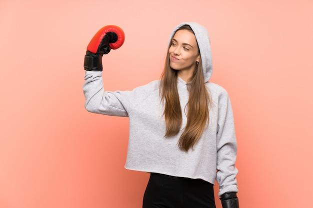 Giovane donna sportiva sopra la parete rosa isolata con guantoni da boxe Foto Premium
