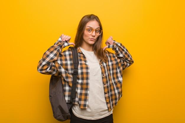 Giovane donna studente che punta le dita, esempio da seguire Foto Premium