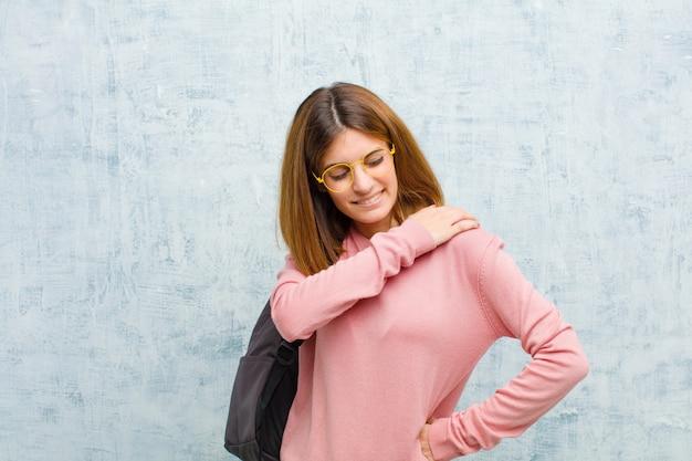 Giovane donna studentessa sentirsi stanca stressata angosciata frustrata e depressa con dolore alla schiena o al collo Foto Premium