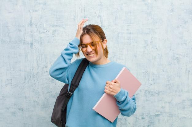 Giovane donna studentessa sentirsi stressata e ansiosa, depressa e frustrata dal mal di testa, alzando entrambe le mani alla testa Foto Premium