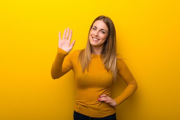 Giovane donna su priorità bassa gialla che saluta con la mano con l'espressione felice Foto Premium