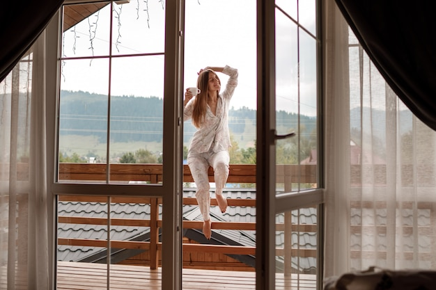 Giovane donna sul balcone che tiene una tazza di caffè o tè al mattino. lei nella camera d'albergo guarda la natura in sumer. la ragazza è vestita in indumenti da notte alla moda. tempo di relax. Foto Premium