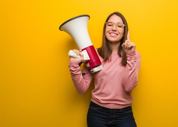 Giovane donna sveglia che tiene un megafono che mostra numero uno Foto Premium