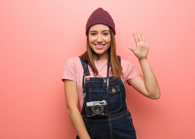 Giovane donna sveglia del fotografo che mostra numero cinque Foto Premium