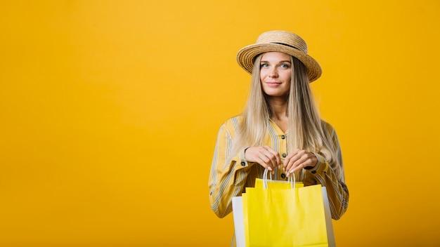 Giovane donna sveglia di vista frontale con le borse Foto Gratuite