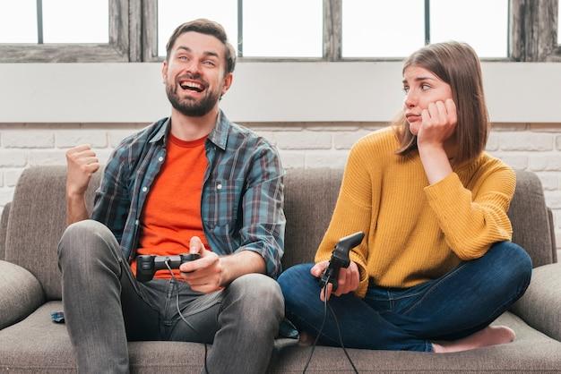 Giovane donna triste che esamina suo marito che gioca il video gioco con la leva di comando Foto Gratuite