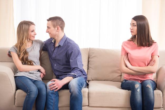 Giovane donna triste che si siede sul divano. Foto Premium