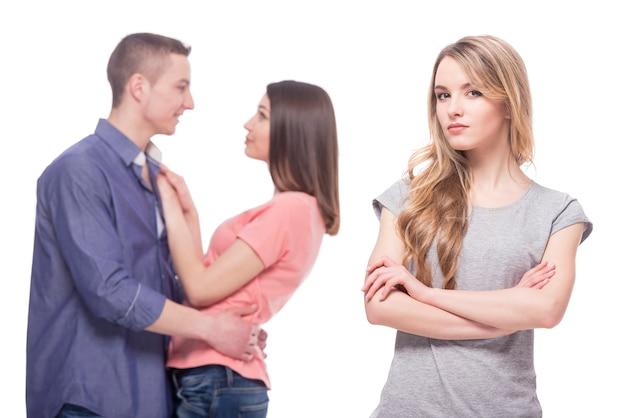 Giovane donna triste in piedi con le braccia incrociate. Foto Premium