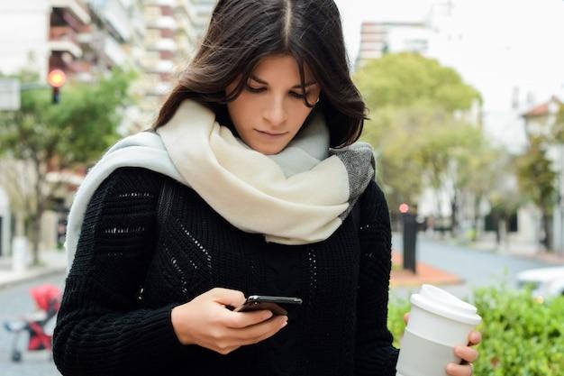 Giovane donna utilizzando uno smartphone Foto Premium