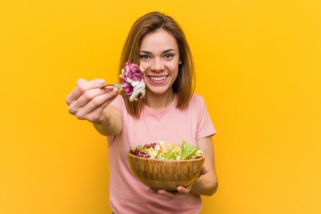 Giovane donna vegana che mangia un'insalata fresca e deliziosa. Foto Premium