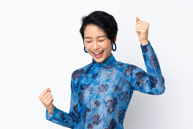 Giovane donna vietnamita con i capelli corti che indossa un abito tradizionale sul muro bianco isolato per celebrare una vittoria Foto Premium