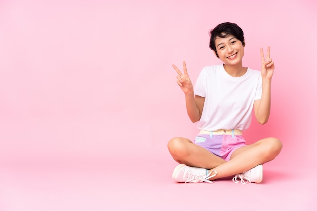 Giovane donna vietnamita con i capelli corti che si siede sul pavimento sopra la parete rosa isolata che mostra il segno di vittoria con entrambe le mani Foto Premium