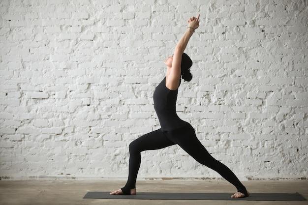 Giovane donna yogi attraente in warrior una posa, loft sfondo Foto Gratuite
