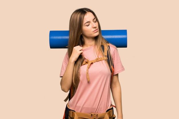 Giovane donna zaino in spalla con espressione stanco e malato su sfondo giallo isolato Foto Premium