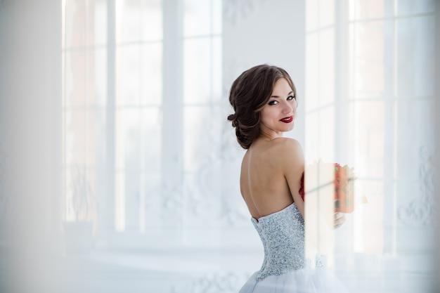 Giovane e bella foto di arte moda di una sposa in abito bianco in salotto. scattati attraverso la porta di vetro, i riflessi creativi leggeri si sovrappongono al ritratto. Foto Premium