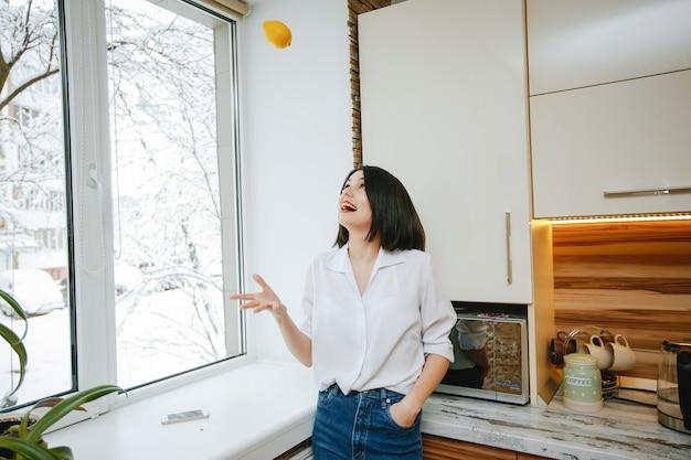 Giovane e bella mora in piedi vicino alla finestra in cucina con il limone Foto Gratuite