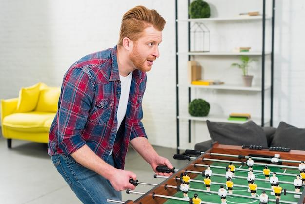Giovane emozionante che gioca il gioco di calcio della tavola di calcio nel salone Foto Gratuite