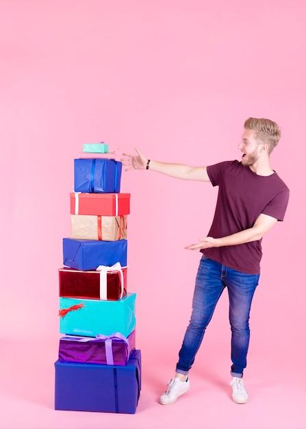 Giovane emozionante che mostra pila di regali variopinti contro il contesto rosa Foto Gratuite
