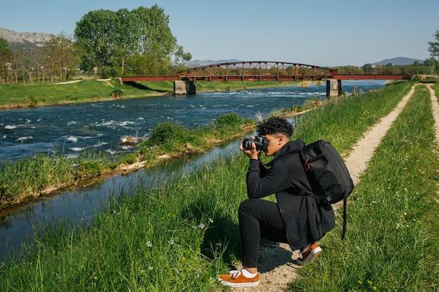 Giovane escursionista che cattura foto del fiume idilliaco Foto Gratuite