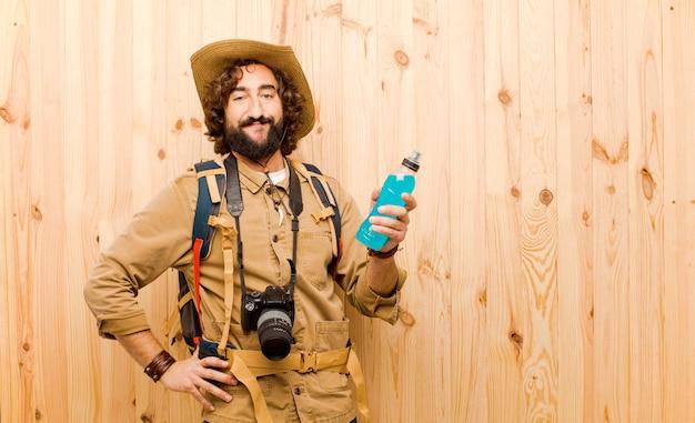 Giovane esploratore pazzo con il cappello di paglia e lo zaino su fondo di legno Foto Premium