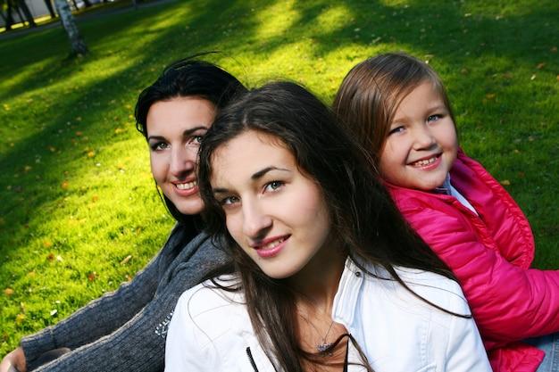 Giovane famiglia che fa passeggiata sana attraverso il parco di autunno Foto Gratuite