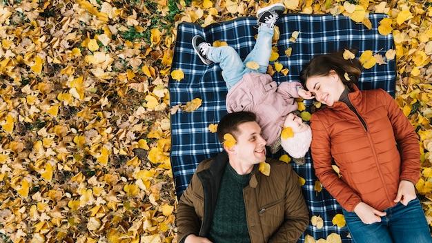Giovane famiglia che si trova sul fogliame di autunno in sosta Foto Gratuite