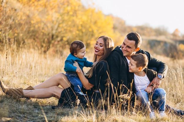 Giovane famiglia con due figli seduti insieme nel parco Foto Gratuite