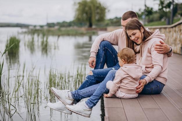 Giovane famiglia con il loro piccolo bambino nel parco in riva al lago Foto Gratuite