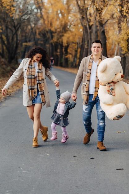 Giovane famiglia con la piccola figlia al giocattolo del grande orso del presente della strada del parco di autunno Foto Premium