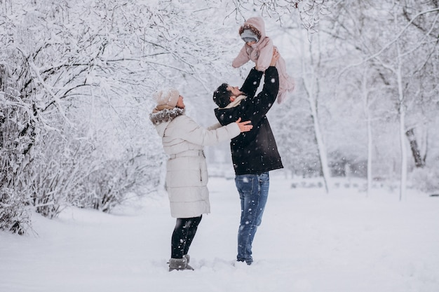 Giovane famiglia con la piccola figlia in una foresta di inverno piena di neve Foto Gratuite